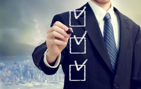Business man checking off checkboxes with cityscape background