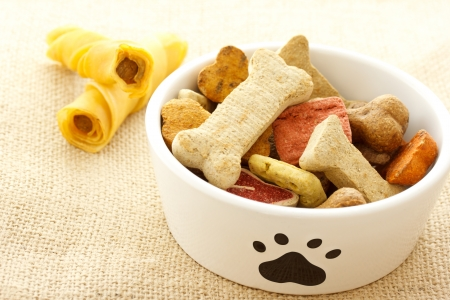 dog biscuit: Dog treats in white bowl on burlap cloth