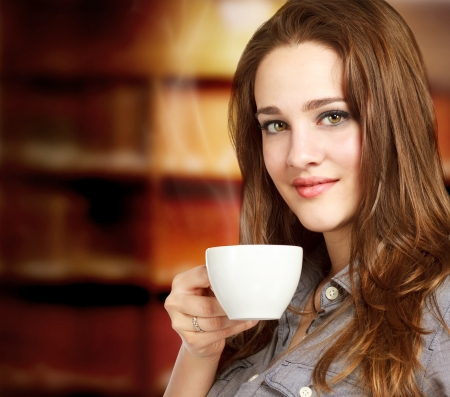 Beautiful Young Women Drinking a Cup of Coffee or Tea photo