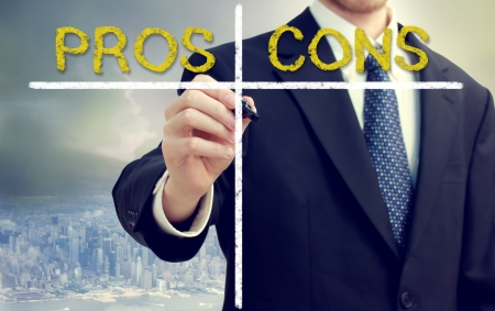Business man writing pros and cons with big city backdrop photo