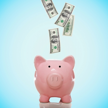 Dollar bills falling in or flying out of a pink piggy bank Stock Photo