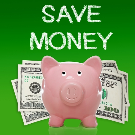 Piggy bank with hundred dollar bills on green background - save money photo