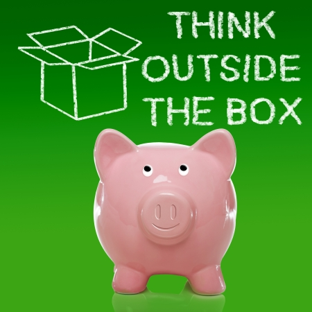 Smiling Piggy bank with thinking outside the box on green background Stock Photo - 18792633