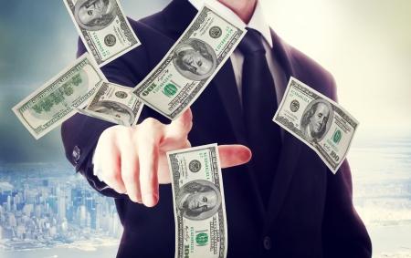 hombre cayendo: Hombre de negocios con billetes de cien d�lares sobre fondo gran ciudad