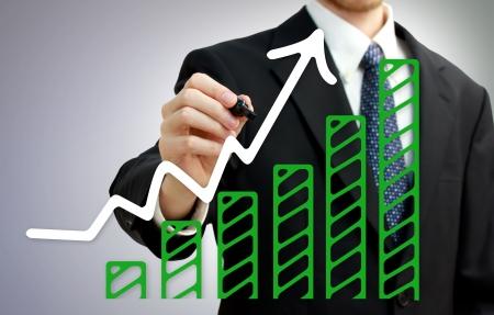 Businessman drawing a rising arrow over growing green bar graph