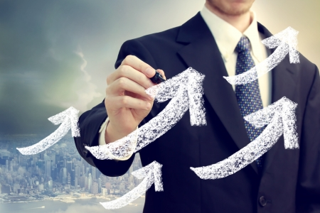 Businessman with rising arrows showing success with big city backdrop photo