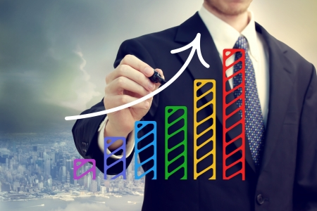 Businessman drawing a rising arrow over a bar graph above the city photo