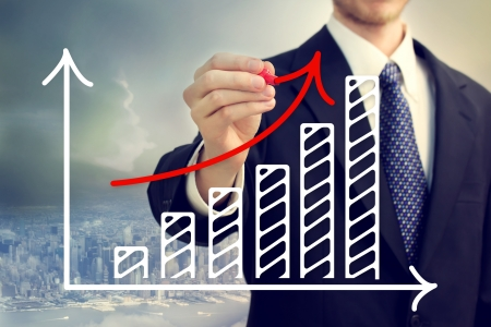 Businessman drawing a rising arrow over a bar graph above the city Stock Photo - 18960949
