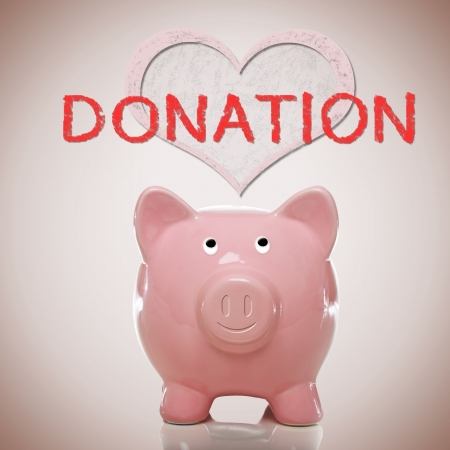 Piggy bank with heart and donation text on pink background photo