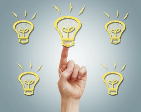 shinning: Female hand pushing light bulb icons on gray background