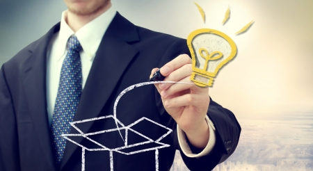 coming out: Business man with Idea light bulb coming out of the box with a big city backdrop Stock Photo