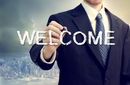bienvenidos: Escritura del hombre de negocios de bienvenida en un backdorp ciudad