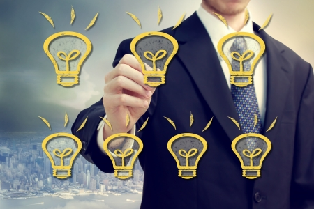 Businessman with light bulbs over city backdrop Stock Photo - 19808661