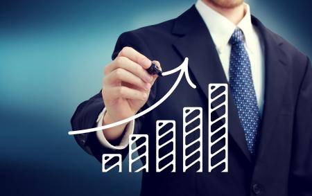 bar graph: Businessman drawing a rising arrow over the bar graph