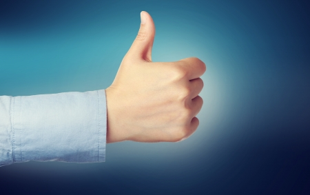 confirmed: Person giving the thumbs up over blue background Stock Photo