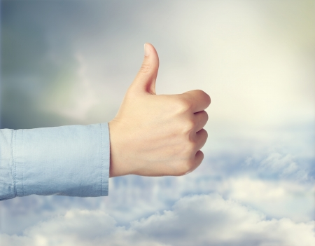 Person giving the thumbs up over cloudscape Stok Fotoğraf