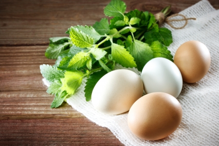 sackcloth: Eggs on a rustic table of wood with a sprig of mint