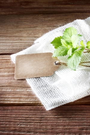 Blank tag on a rustic wooden table with burlap and a sprig of mint  Stock fotó