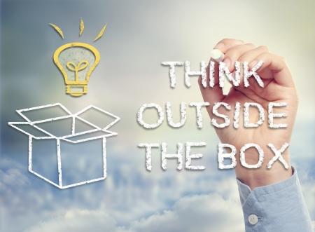 Denk buiten de doos concept met idee gloeilamp en open doos tekening in krijt Stockfoto