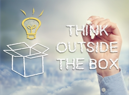 Think outside the box concept with idea lightbulb and open box drawing in chalk Stok Fotoğraf