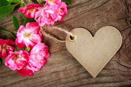 Handmade heart shaped tag with robin hood roses on a rustic wooden table  photo