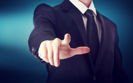Business man with pointing to something or touching a touch screen on blue background