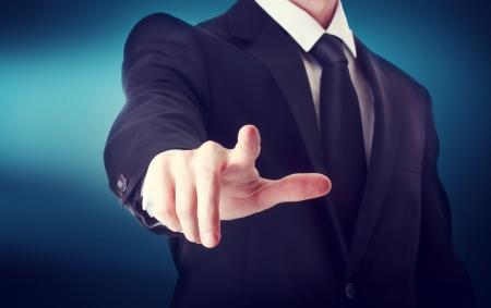 dedo apuntando: Hombre de negocios con el que apunta a algo o tocar una pantalla táctil sobre fondo azul
