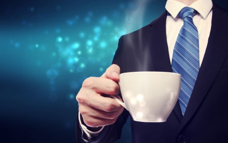 navy blue suit: Business man holding a steaming cup of hot coffee on blue modern background
