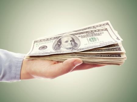 緑の背景の手で開催された 100 ドル札の札束
