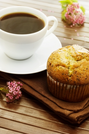 Delicious poppy seed muffins and  a cup of coffee with pink small flowers
