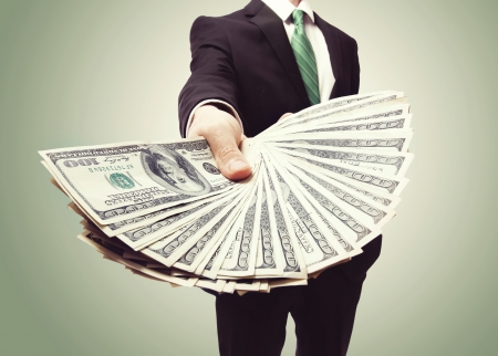 ビジネスの男性緑ビンテージ背景上の現金広がりを表示します。