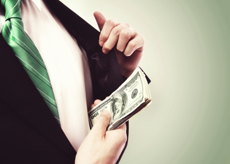 hand in pocket: Business Man putting  a wad of cash in his suit jacket pocket on green vintage background Stock Photo