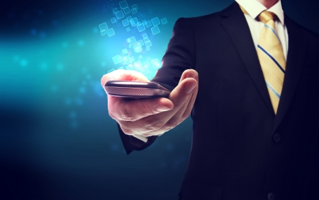 Business man with a mobile phone on a modern technology background photo