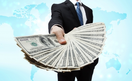 Business Man Displaying a Spread of Cash over blue world map background photo