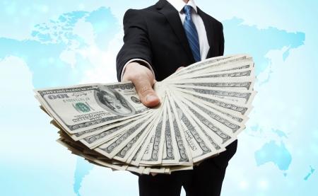 Business man met een spreiding van Cash over blauwe wereld kaart achtergrond Stockfoto