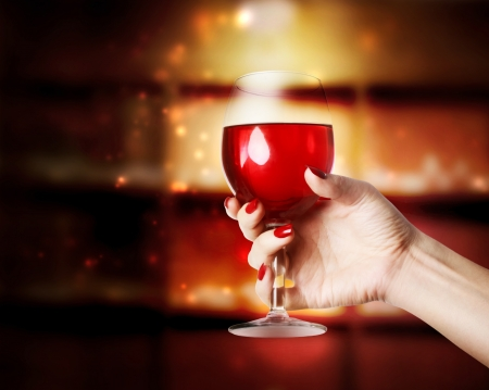 Glass of Red Wine in a young womans hand Stock Photo - 21688891