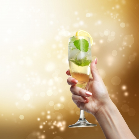 Champagne glass being lifted up in the air by a young woman on golden shinning background photo