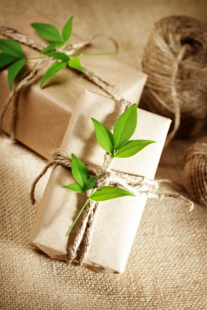 wrapped present: Natural style handcrafted gift boxes with rustic twine on burlap