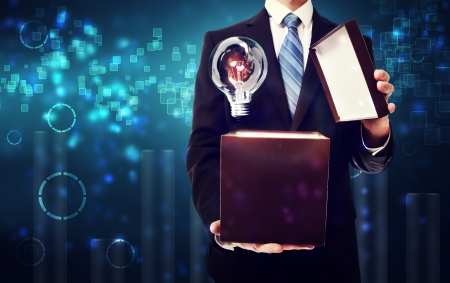 Business man opening box with an idea lightbulb on blue technology background photo