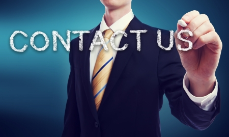 write us: Business Man Writing Contact Us in Chalk with Glowing Blue Background