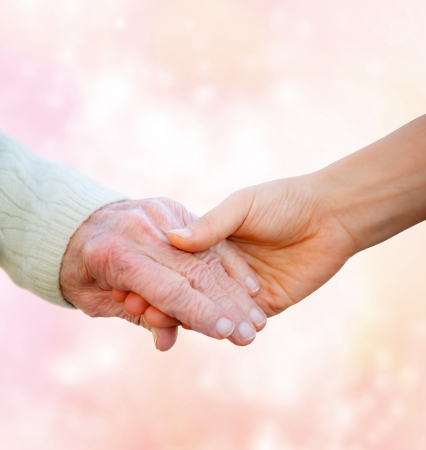 Senior Lady Holding Hands with Young Woman  photo