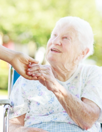 caretaker: Senior woman in a wheelchair outside holding hands with her caretaker