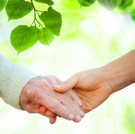 Hand in hand met senior over groene bladeren