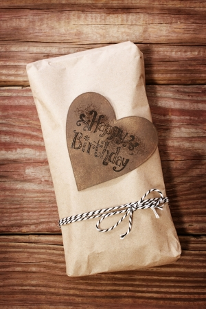 Hand crafted happy birthday present box on rustic wooden boards photo