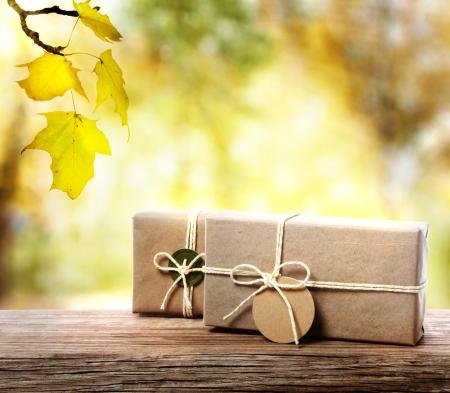 motouz: Handcrafted dárkové krabice na starých dřevěných desek s podzimní listí Reklamní fotografie