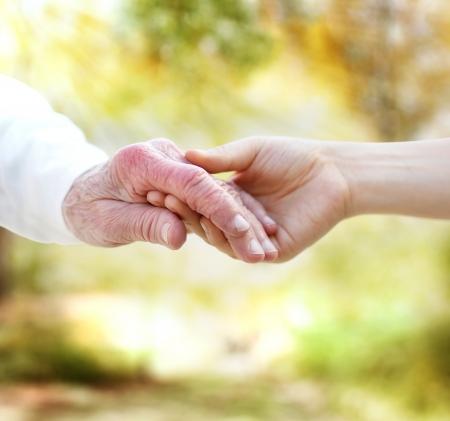 manos sosteniendo: Tomados de la mano con la alta en el otoño de hojas amarillas