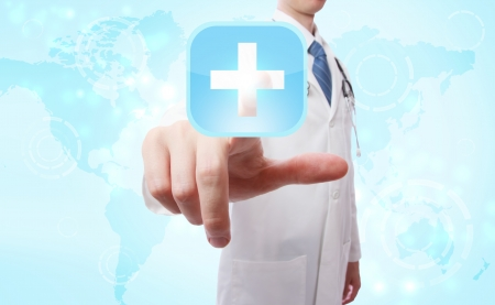 Medical Doctor pushing a blue cross icon over world map background photo