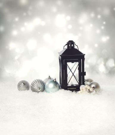 Kerst lantaarn en ornamenten op de sneeuw in een zilveren stralende nacht Stockfoto