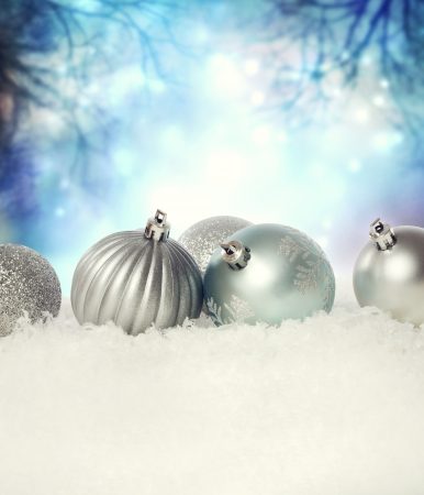 Silver Christmas baubles on the snow in the night photo