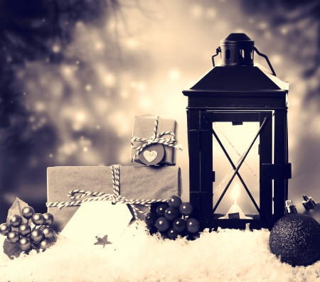 Christmas lantern with presents, ornaments and snow in sepia tone photo